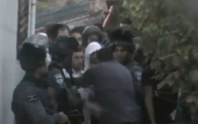 Israel security forces escort five yeshiva students from a Palestinian home in Hebron on August 3, 2015, where they had been offered shelter after their presence in the West Bank city sparked riots. (screen capture: NRG website)