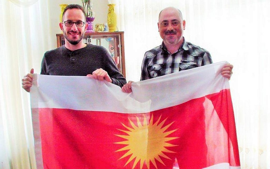 Idan Barir and a member of the Yazidi resistance hold a Yazidi flag. (Courtesy)