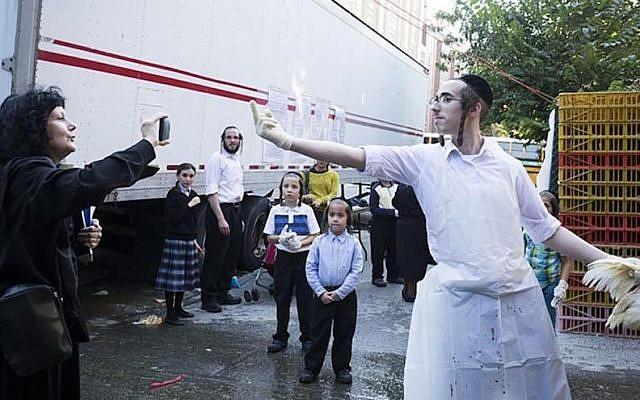 A Hasidic man expressing his views to an anti-kapparot activist in Brooklyn, New York, Sept. 17, 2015. (JTA)
