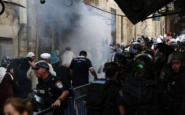 Security forces stand guard as Palestinians walk away from tear gas smoke during clashes between Palestinians and Israeli police at Al-Aqsa mosque compound in Jerusalem's Old City, September 13, 2015. (AFP/AHMAD GHARABLI)