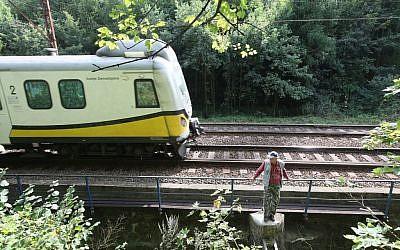 A man stands by the rail tracks near a place where a legend says a Nazi train with gold might be hidden near Walbrzych, Poland, on Wednesday, September 2, 2015. (Czarek Sokolowski/AP)