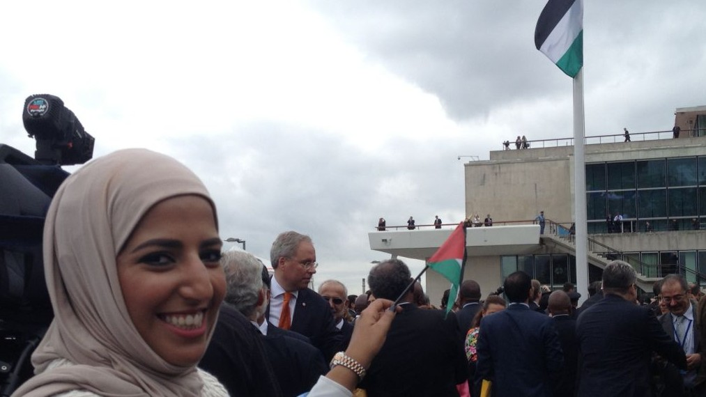 A woman smiles and waves a small Palestinian flag as the Palestinian banner is raised outside UN Headquarters in New York during the 70th Session of the UN General Assembly on September 30, 2015 (Raphael Ahren)