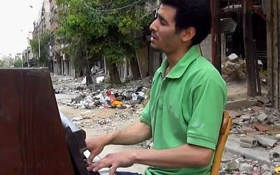 Aeham al-Ahmad plays piano amid the rubble of the Yarmouk refugee camp in Syria, August, 2015 (YouTube screenshot)