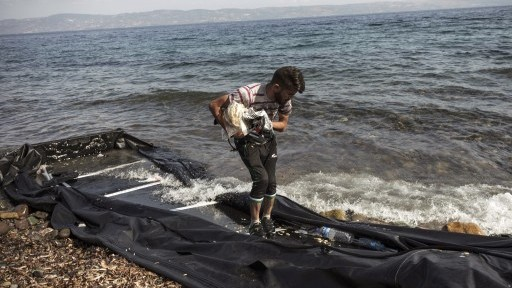 A Syrian migrant collects his belongings as he arrives on the shore of Lesbos island, after crossing the Aegean sea from Turkey on an inflatable boat on August 22, 2015. (AFP PHOTO / ACHILLEAS ZAVALLIS)
