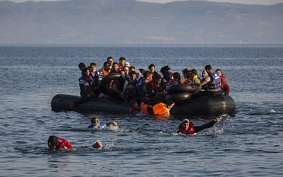 An illustrative image of migrants swimming from an overcrowded dinghy on July 27, 2015. (AP/Santi Palacios)