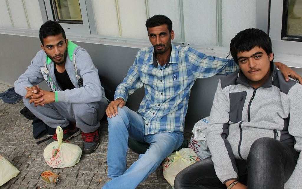 Syrian refugee Khalid el-Hassan, right, spent more than 10 days trying to register with authorities after arriving in Berlin, September 17, 2015. (Uriel Heilman/JTA)