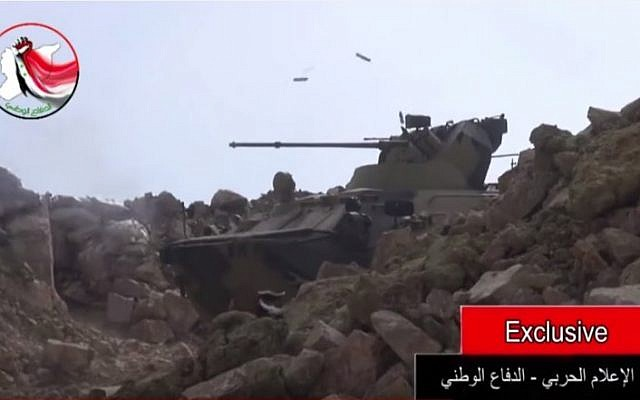 An armored personnel carrier, likely a Russian made BTR-82A, firing large-caliber bullets during a battle in Latakia, Syria, is seen in a video posted online on August 23, 2015. (Screen capture YouTube)