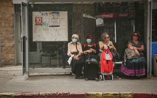Israelis cover their mouths at a bus stop in Jerusalem on September 8, 2015. (Photo by Hadas Parush/Flash90)