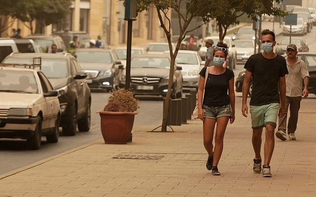 Lebanese citizens, cover their face with masks during a sandstorm, in downtown Beirut, Lebanon, Tuesday, Sept. 8, 2015. (AP Photo/Bilal Hussein)
