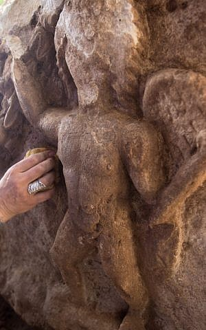 An Israel Antiquities Authority (IAA) worker cleans naked cupids on a unique Roman-era sarcophagus at a warehouse in Bet Shemesh on September 3, 2015. (AFP PHOTO/MENAHEM KAHANA)