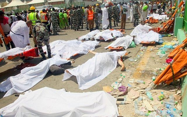 Saudi emergency personnel and pilgrims stand near bodies covered in sheets at the site where hundreds were killed in a stampede in Mina, near the holy city of Mecca, at the annual hajj in Saudi Arabia on September 24, 2015. (AFP/STR)