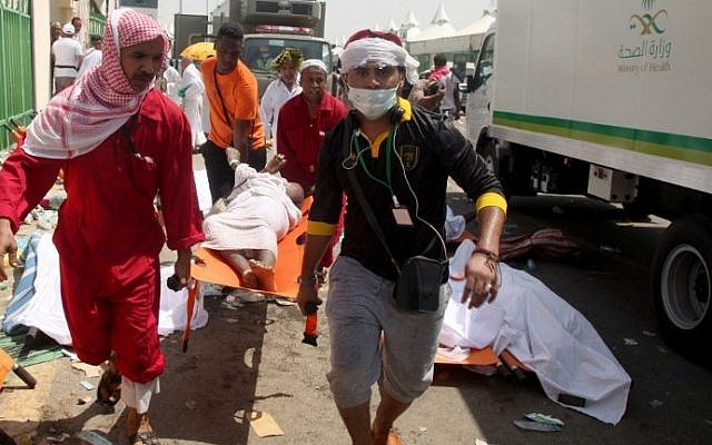 Saudi emergency personnel and Hajj pilgrims carry a wounded person at the site where hundreds  were killed in a stampede in Mina, near the holy city of Mecca, at the annual hajj in Saudi Arabia on September 24, 2015.  (AFP/ STR)