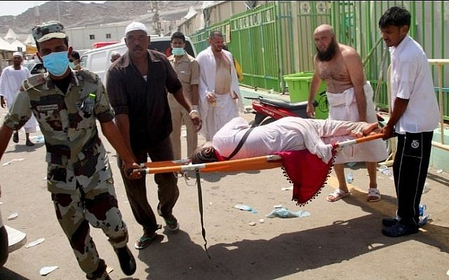 Hajj pilgrims and Saudi emergency personnel carry a woman on a stretcher at the site where hundreds were killed in a stampede in Mina, near the holy city of Mecca, at the annual hajj in Saudi Arabia on September 24, 2015. (AFP/STR)