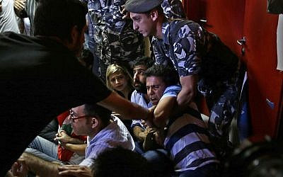 A Lebanese policeman, right, tries to drags away an anti-government activist during a sit-in protest against Environment Minister Mohammed Machnouk, inside the Environment Ministry, in downtown Beirut, Lebanon, Tuesday, September 1, 2015. (Hassan Ammar/AP)