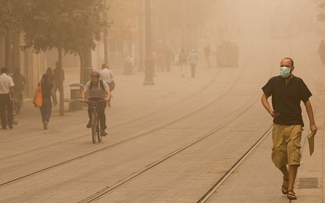 Israelis walk across the lightrail tracks on Jerusalem's Jaffa Road on September 8, 2015 during a sandstorm. (Yonatan Sindel/Flash90)