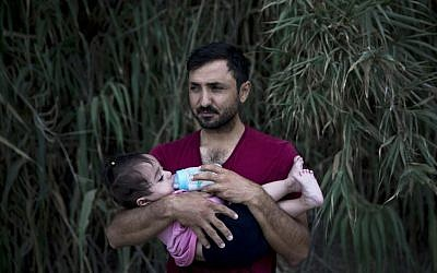 A Syrian refugee feeds milk to his daughter after they arrived on a dinghy, from Turkey to Lesbos island, Greece, Wednesday, Sept. 9, 2015. (AP Photo/Petros Giannakouris)