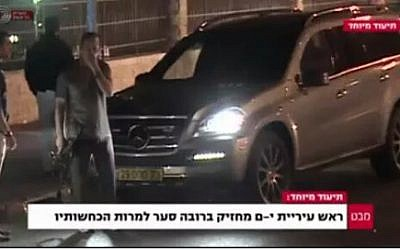 A screen capture from Israel's Channel 1 shows Jerusalem Mayor Nir Barkat with a gun. The caption reads, 'Jerusalem mayor carries assault rifle, despite his denials.'
