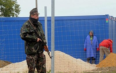 A soldier of the Hungarian Army stands guard at the Beremend border station on September 30, 2015, as workers prepare a container base for a new transit zone.  (AFP Photo/Laszlo Laufer)