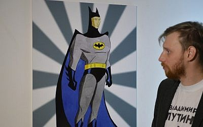 "A visitor looks at an artwork depicting Russian President Vladimir Putin as Batman during the ""Putin Universe"" exhibition in Moscow on October 6, 2015. (Natalia Kolesnikova/AFP)"