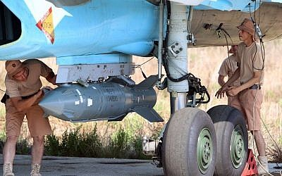 A picture taken on October 3, 2015, shows Russian air force technicians checking a Russian Su-34 fighter bomber at the Hmeimim airbase in the Syrian province of Latakia. (AFP/Komsomolskaya Pravda/Alexander Kots)