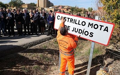 Officials look at an employee setting up a road sign reading the new name of Spanish village 'Castrillo Mota de Judios' which means 'Castrillo Mound of Jews'  at the entrance of Castrillo Mota de Judios, near Burgos on October 23, 2015. (AFP PHOTO/ CESAR MANSO)