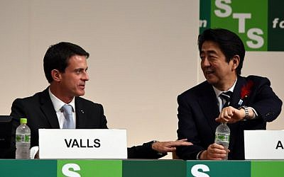 French Prime Minister Manuel Valls, left speaks to Japan's Prime Minister Shinzo Abe while attending the opening session of the Science and Technology in Society forum in Kyoto on October 4, 2015. (AFP/TOSHIFUMI KITAMURA)