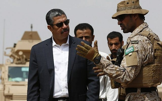 A member of the Saudi forces speaks to Yemeni Prime Minister Khaled Bahah (L) during his visit to the Saudi-led coalition military base  (AFP PHOTO / AHMED FARWAN)