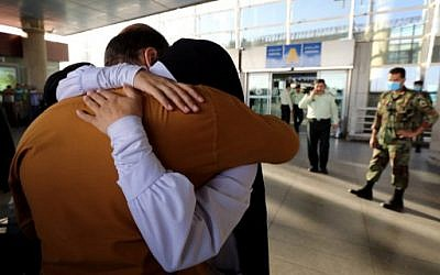 An Iranian woman cries as she hugs her husband at the Imam Khomeini international airport in Tehran following her return from the hajj pilgrimage in Saudi's holy Muslim city of Mecca, September 29, 2015. (AFP/ATTA KENARE)