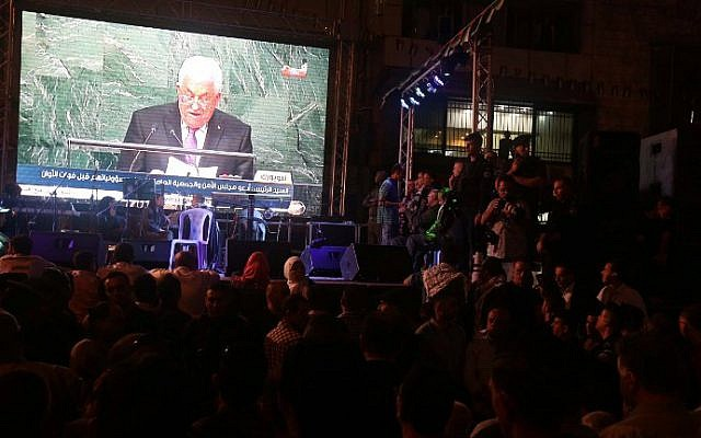 Palestinians watch the speech of PA President Mahmoud Abbas on a giant screen in Ramallah as he addresses the world at the United Nations headquarters in New York on September 30, 2015. (AFP/Jaafar Ashtiyeh)