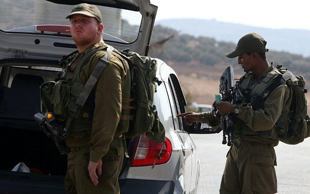 Israeli soldiers inspect a Palestinian car at a checkpoint close to the West Bank village of Beit Furik, east of Nablus, on October 2, 2015, after Palestinian gunmen killed an Israeli couple the night before. (AFP/Jaafar Ashtiyeh)