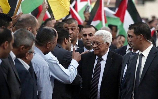 Palestinians wave their national flags as they greet Palestinian Authority president Mahmud Abbas upon his arrival from New York on October 2, 2015 where he attended a ceremony to mark the raising of the Palestinian flag at the United Nations headquarters, in the city of Ramallah. (Abbas Momani/AFP)