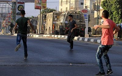 Palestinian protesters hurl rocks at IDF soldiers on a street, east of the West Bank city of Nablus, on October 3, 2015, as they search for the suspected Palestinian killers of an Israeli couple. (AFP PHOTO/JAAFAR ASHTIYEH)