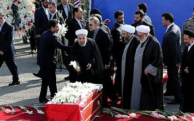 Iranian President Hassan Rouhani (center) places flowers on the caskets of Iranian pilgrims, killed in a stampede at the annual hajj, during a repatriation ceremony upon their arrival on October 3, 2015 at Tehran's Mehrabad Airport. (AFP PHOTO/ATTA KENARE)