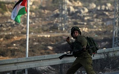 An Israeli soldier hurls a smoke grenade during clashes with Palestinian youth close to the Jewish settlement of Bet El, in the West Bank city of Ramallah on October 4, 2015. (AFP/ABBAS MOMANI)