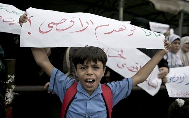"A Palestinian boy holds up a banner reading in Arabic ""What if they destroy al-Aqsa"" during a demonstration in Rafah, in the southern Gaza Strip, on October 5, 2015 (Said Khatib/AFP)"