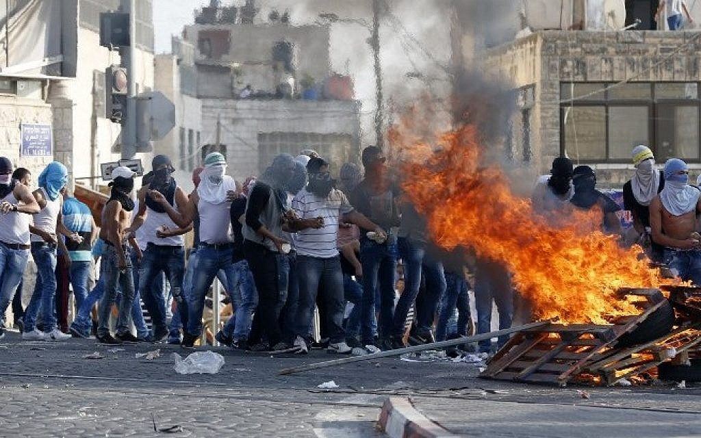 Palestinian stone throwers stand next to burning wood during clashes with Israeli security forces in Shuafat in East Jerusalem on October 5, 2015. (AFP/Ahmad Gharabli)