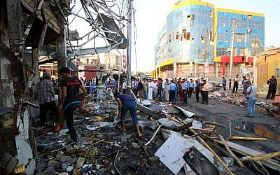 Iraqis gather at the site of a car bomb attack that hit the day before a market area known as Souk al-Halaqin in Zubayr, just 10 kilometers (six miles) southwest of the oil hub of Basra on October 6, 2015. (AFP/HAIDAR MOHAMMED ALI)