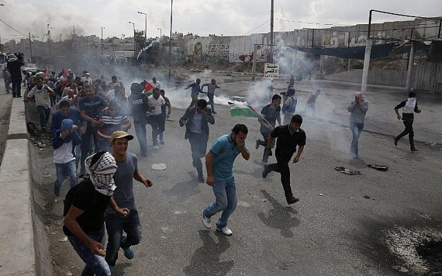 File. Palestinians run from tear gas smoke during clashes with Israeli security forces at the Qalandia checkpoint between Jerusalem and Ramallah in the West Bank, on October 6, 2015. (AFP PHOTO/ABBAS MOMANI)