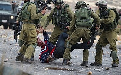 Israeli soldiers detain a Palestinian stone thrower near Beit El, on the outskirts of the West Bank city of Ramallah, on October 7, 2015. (AFP/ABBAS MOMANI)