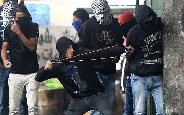 A Palestinian protester uses a slingshot to throw stones towards Israeli security forces during clashes in the West Bank town of Hebron on October 7, 2015. (AFP/Hazem Bader)