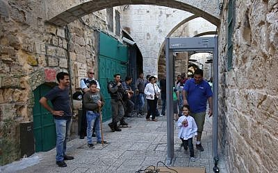 Tourists walk past a metal detector in the Muslim Quarter of Jerusalem's Old City on October 8, 2015 following a spate of knife attacks. (AFP Photo / Gali Tibon)