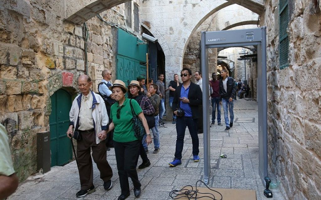 Tourists walk past a metal detector in the Muslim quarter of Jerusalem's Old City on October 8, 2015 following a spate of knife attacks. (AFP Photo/Gali Tibon)
