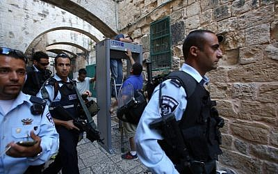 Israeli security forces stand guard as workers install a metal detector in the Muslim quarter of Jerusalem's Old City on October 8, 2015. (AFP/GALI TIBON)