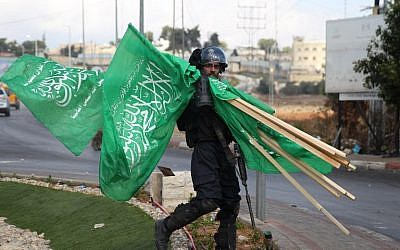 A member of Israeli security forces carries flags of the Hamas terror group that were seized during clashes with Palestinian protesters near the West Bank Jewsih settlement of Beit El on October 8, 2015. (AFP/ABBAS MOMANI)
