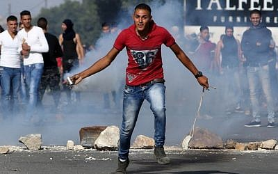 A Palestinian protester throws back a tear gas canister during clashes with Israeli soldiers at the Hawara checkpoint, south of the West Bank city of Nablus on October 9, 2015. (AFP PHOTO/JAAFAR ASHTIYEH)