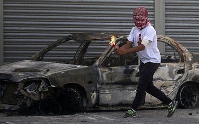 A Palestinian protester prepares to throw a firebomb during clashes with Israeli security forces in the Shuafat refugee camp in East Jerusalem, on October 9, 2015. (Ahmad Gharabli/AFP)