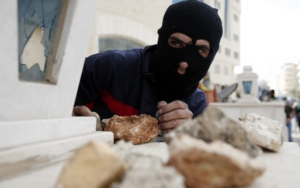 A Palestinian stone thrower looks on during clashes with Israeli security forces in Beit El, near the West Bank city of Ramallah on October 10, 2015. (AFP/ABBAS MOMANI)