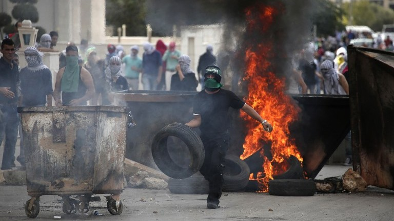 Illustrative photo of a Palestinian protester burning tires during clashes with Israeli security forces in the West Bank on October 10, 2015. (AFP/ABBAS MOMANI)