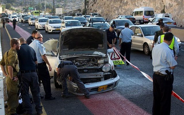 Israeli police inspect the damaged car of a Palestinian woman after she detonated a small bomb on October 11, 2015 on the highway leading from Ma'ale Adumim to Jerusalem. (AFP PHOTO/MENAHEM KAHANA)