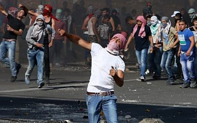 Masked Palestinian protesters clash with Israeli security forces at the Hawara checkpoint, south of the West Bank city of Nablus, on October 11, 2015. (AFP/Jaafar Ashtiyeh)